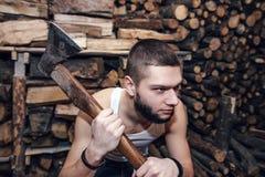 Hombre con un hacha cerca de la acción de la leña, foco en el hacha Foto de archivo libre de regalías