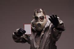 Hombre con un juego del hazmat de la careta antigás que desgasta, sosteniéndose imagenes de archivo