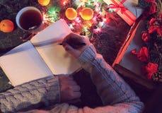 Hombre con un libro en blanco en sus manos para la tabla del ` s del Año Nuevo con Foto de archivo libre de regalías
