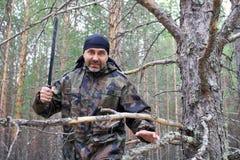 Hombre con un machete en el bosque Imagenes de archivo
