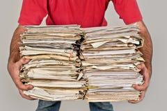 Hombre con un manojo de periódicos viejos en las manos Imagen de archivo libre de regalías