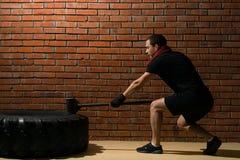 Hombre con un martillo en sus golpes de la mano en un neumático, crossfit de entrenamiento contra una pared de ladrillo imagen de archivo