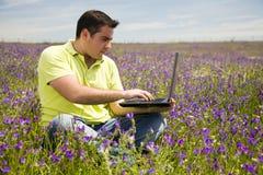 Hombre con un ordenador portátil Fotos de archivo