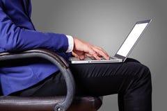 Hombre con un ordenador portátil que se sienta en oficina fotos de archivo