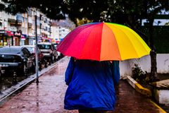Hombre con un paraguas colorido que camina en una calle lluviosa Foto de archivo