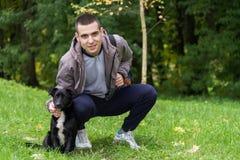 Hombre con un perro en la hierba imagen de archivo
