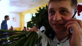 Hombre con un ramo grande de flores que habla en el teléfono y que sonríe, cámara lenta