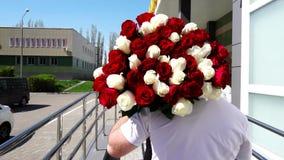 Hombre con un ramo grande de rosas coloridas que mueven la visión desde la parte posterior, cámara lenta