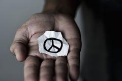 Hombre con un símbolo de paz en un trozo de papel Imagenes de archivo