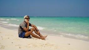 Hombre con un teléfono celular en la playa imagenes de archivo