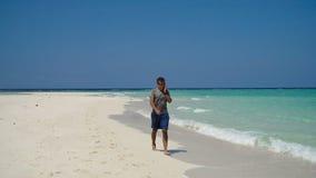 Hombre con un teléfono celular en la playa metrajes