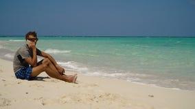 Hombre con un teléfono celular en la playa almacen de video