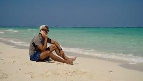 Hombre con un teléfono celular en la playa almacen de metraje de vídeo
