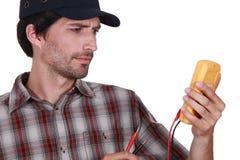 Hombre con un voltímetro foto de archivo