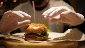 Hombre con una barba que se prepara para comer una hamburguesa cheeseburger almacen de video
