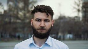 Hombre con una barba y corte de pelo hermoso en una calle en el primer 4k de la ciudad almacen de metraje de vídeo