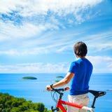 Hombre con una bici en fondo hermoso de la naturaleza Fotos de archivo libres de regalías