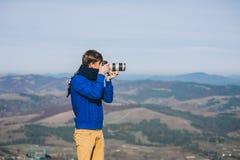 Hombre con una cámara en el borde de un acantilado que pasa por alto las montañas Fotografía de archivo libre de regalías