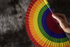 Hombre con una fan arco iris-modelada de la mano Foto de archivo libre de regalías