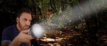 Hombre con una linterna en el bosque imagenes de archivo
