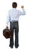 Hombre con una maleta que golpea en puerta imaginaria Imágenes de archivo libres de regalías