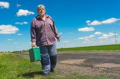 Hombre con una maleta verde que camina en una carretera nacional Imagen de archivo