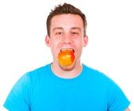 Hombre con una manzana en su boca Fotos de archivo libres de regalías
