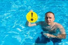 Hombre con una marca de exclamación en la piscina Imágenes de archivo libres de regalías