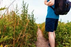 Hombre con una mochila que camina abajo de un rastro Fotografía de archivo