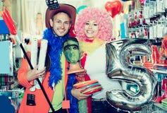 Hombre con una mujer que demuestra los accesorios para el día de fiesta Foto de archivo libre de regalías