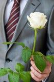 Hombre con una rosa blanca Foto de archivo libre de regalías