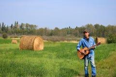 Hombre con a y guitarra acústica en el campo imagen de archivo libre de regalías
