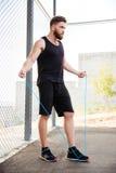 Hombre concentrado de la aptitud que hace ejercicios cardiios con la cuerda que salta al aire libre Imagenes de archivo