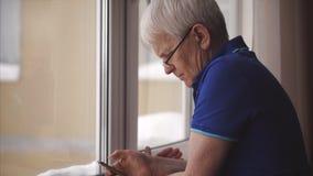 Hombre concentrado mayor en vidrios que escribe el mensaje en su smartphone a estrenar metrajes