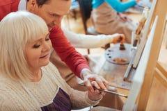Hombre concentrado que ayuda a la mujer mayor en estudio de la pintura Imagen de archivo