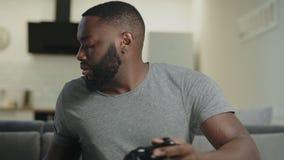 Hombre concentrado que juega al juego en la cocina Individuo frustrado que sostiene Playstation almacen de video