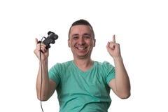 Hombre concentrado que juega a los videojuegos en un fondo blanco Foto de archivo libre de regalías