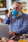 Hombre concentrado que mecanografía algo en el ordenador portátil mientras que teniendo un t Foto de archivo libre de regalías