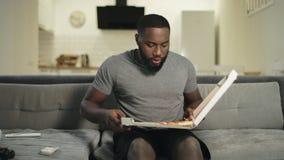 Hombre concentrado que mira la pantalla de la TV Pizza que muerde feliz del fanático del fútbol metrajes