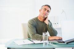 Hombre concentrado que trabaja con el ordenador portátil Fotos de archivo libres de regalías