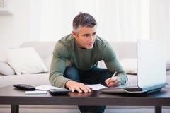 Hombre concentrado que usa el ordenador portátil y tomando notas Fotos de archivo