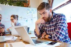 Hombre concentrado que usa el ordenador portátil mientras que sus amigos que estudian junto Fotografía de archivo libre de regalías