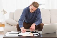 Hombre concentrado que usa la calculadora que cuenta sus cuentas Imágenes de archivo libres de regalías