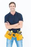 Hombre confiado con la correa de la herramienta alrededor de la cintura sobre el fondo blanco Foto de archivo libre de regalías