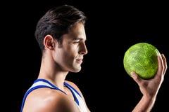 Hombre confiado del atleta que sostiene una bola Imagen de archivo