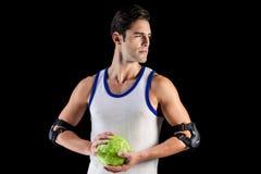 Hombre confiado del atleta que sostiene una bola Fotos de archivo