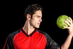 Hombre confiado del atleta que sostiene una bola Foto de archivo libre de regalías