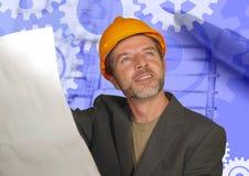 Hombre confiado del ingeniero industrial en casco del constructor que comprueba modelos de la construcción de edificios en el des imagen de archivo libre de regalías