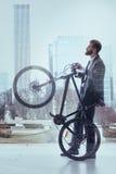 Hombre confiado en bicicleta del montar a caballo del traje en ciudad imaginable Foto de archivo