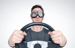 Hombre confiado en gafas elegantes con el volante, concepto del conductor de coche fotografía de archivo